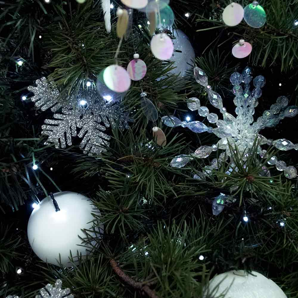 Christmas trees decorated in silver and white with eco office plants